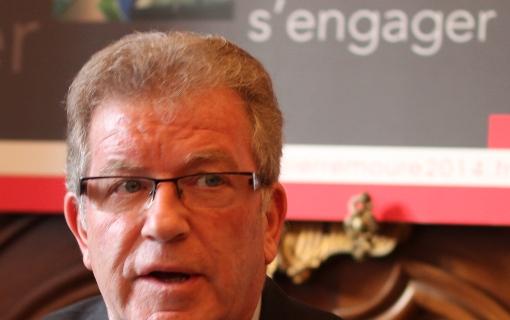 """Jean-Pierre Moure le 17 décembre 2013. Derrière le candidat PS-EELV, il est écrit : """"S'engager."""" (photo : J.-O. T.)"""